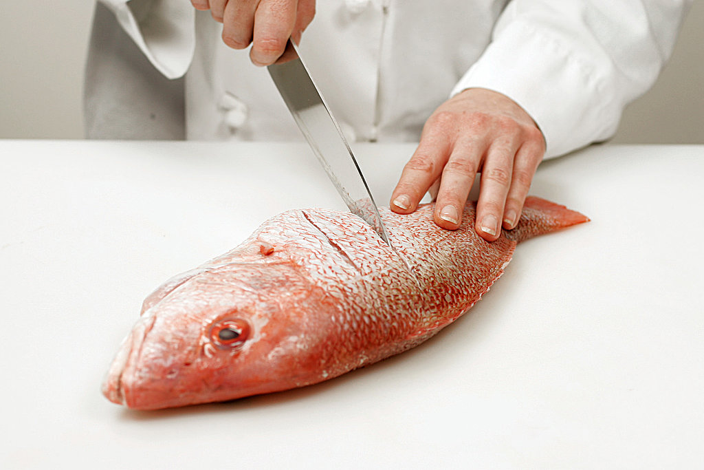Use a sharp knife to make shallow diagonal slashes every 2 inches along both sides of the fish, beginning just behind the dorsal fin. This helps to ensure even cooking and also allows the cook to check the flesh for doneness.