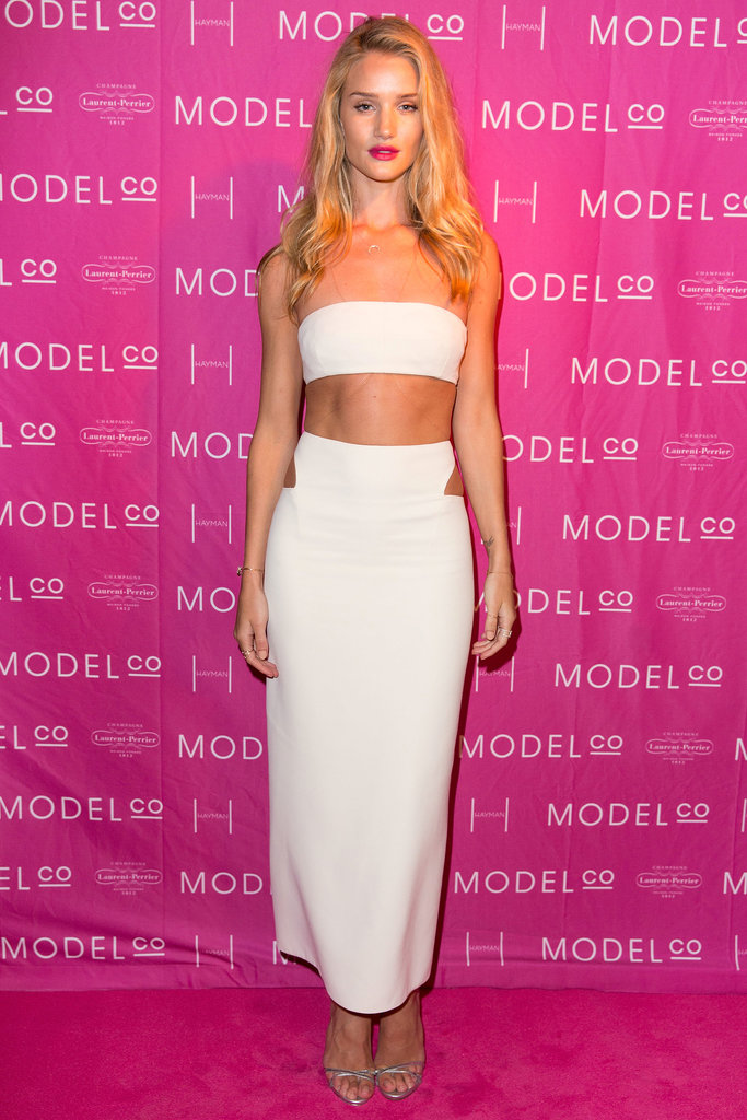 Rosie Huntington-Whiteley put her svelte figure on display in a white Calvin Klein Collection ensemble, which included a sexy crop top balanced by a midi-length cutout skirt.
