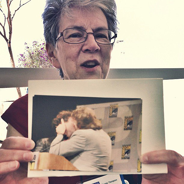 This is Maggie Thompson, longtime editor of Comics Buyer's Guide, holding a picture of Neil Gaiman and Jonathan Ross (gasp!) sharing a snog at the Eisner Awards.