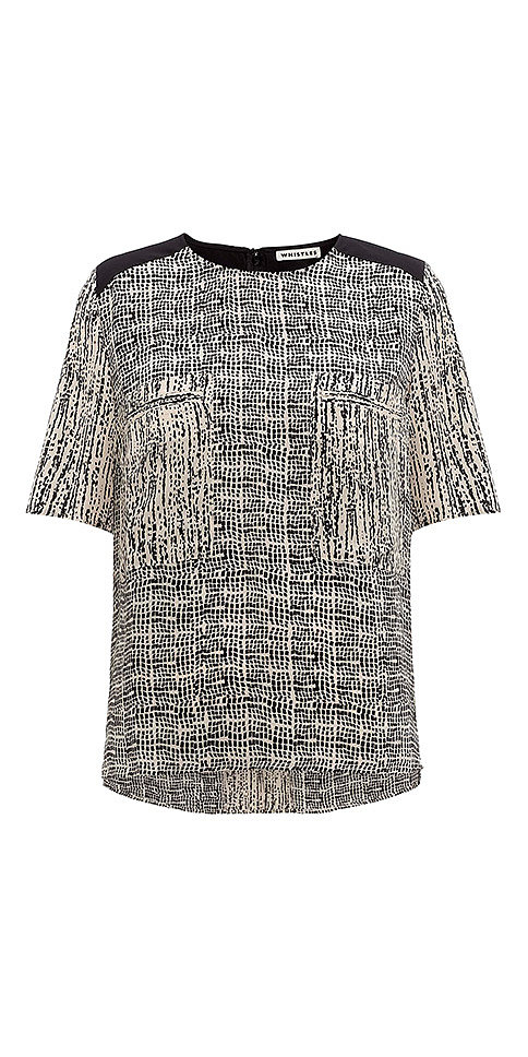 A printed silk top ($157) from Whistles would look smashing with her dark denim.