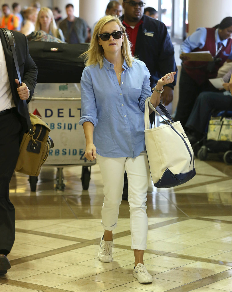 Preppy met cool in Reese Witherspoon's travel style. Follow her lead by pairing a chambray button-down with white denim, white sneakers, and a canvas tote.