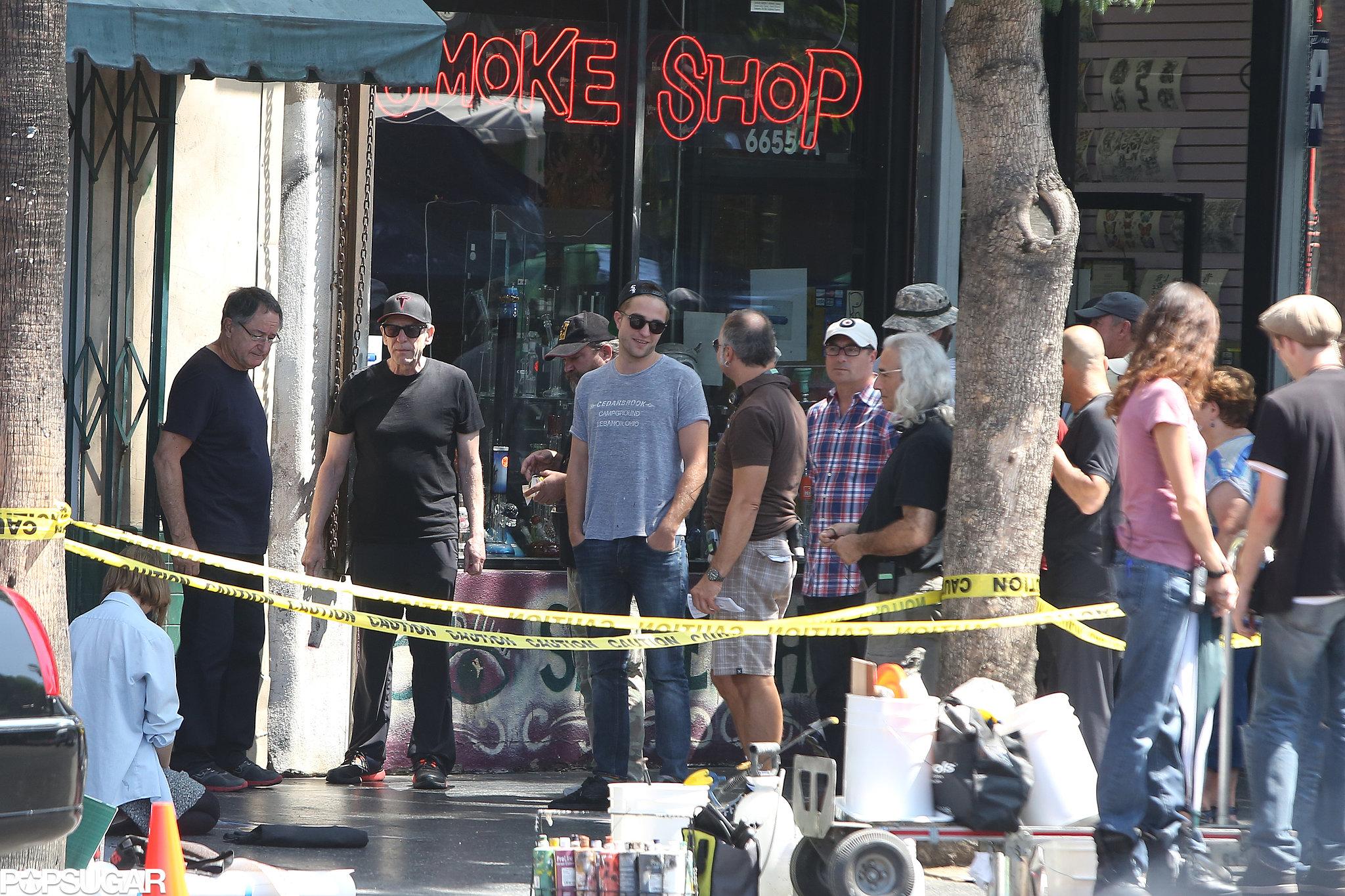 Robert Pattinson wore a gray t-shirt and a backwards hat on set.