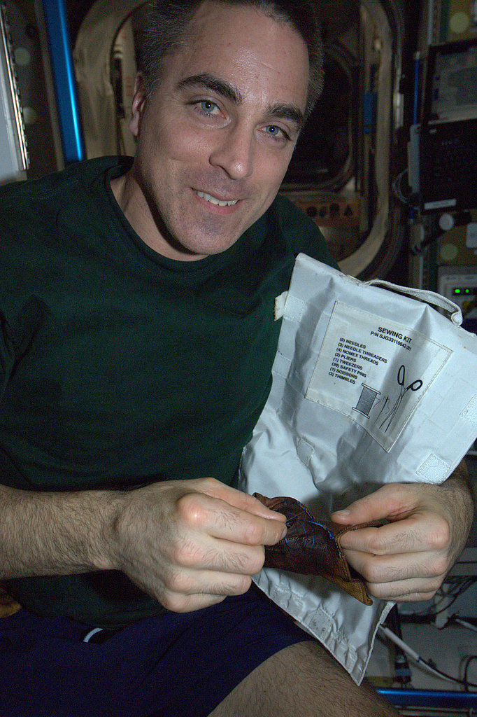 """""""Sewing — an important expeditionary skill! My crewmate Chris Cassidy mends a weightlifting glove (no running to the store for new ones) that should now last until he leaves the Space Station in September. KN from space.""""  Source: Pinterest user Karen Nyberg"""