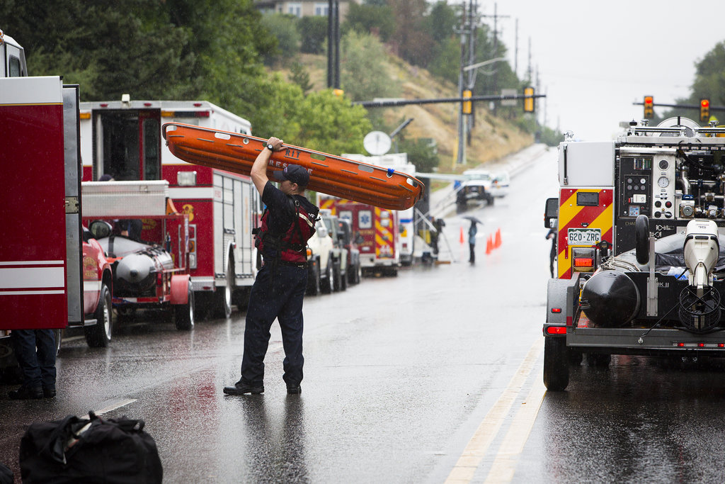 Policemen and firefighters gathered to help people who were caught on the roads of Boulder, CO, after a flash flood.
