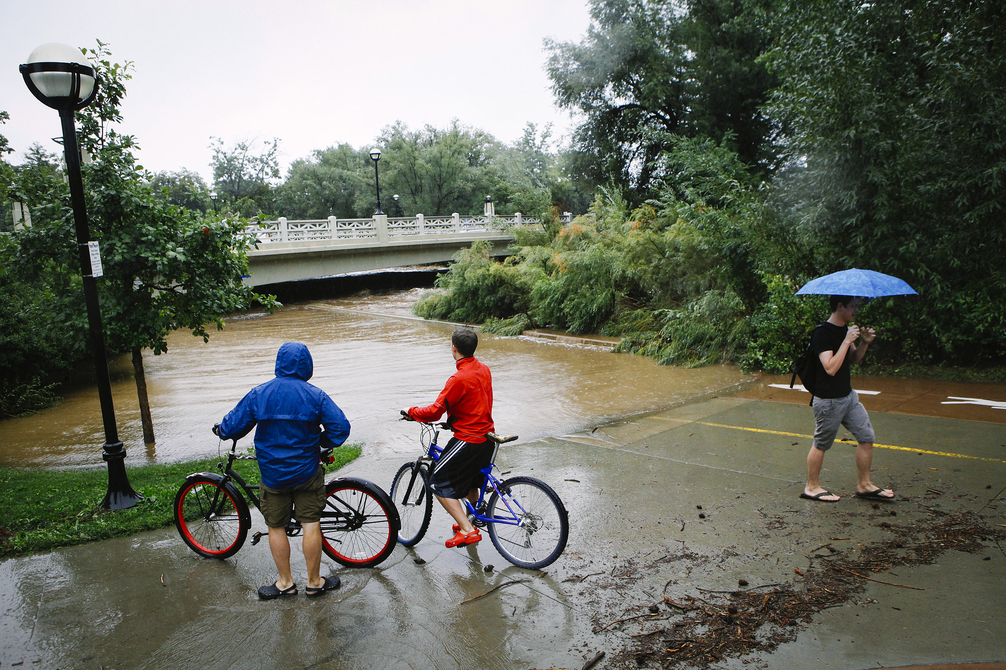 People checked out the overflowing waters of Boulder Creek as they passed by.