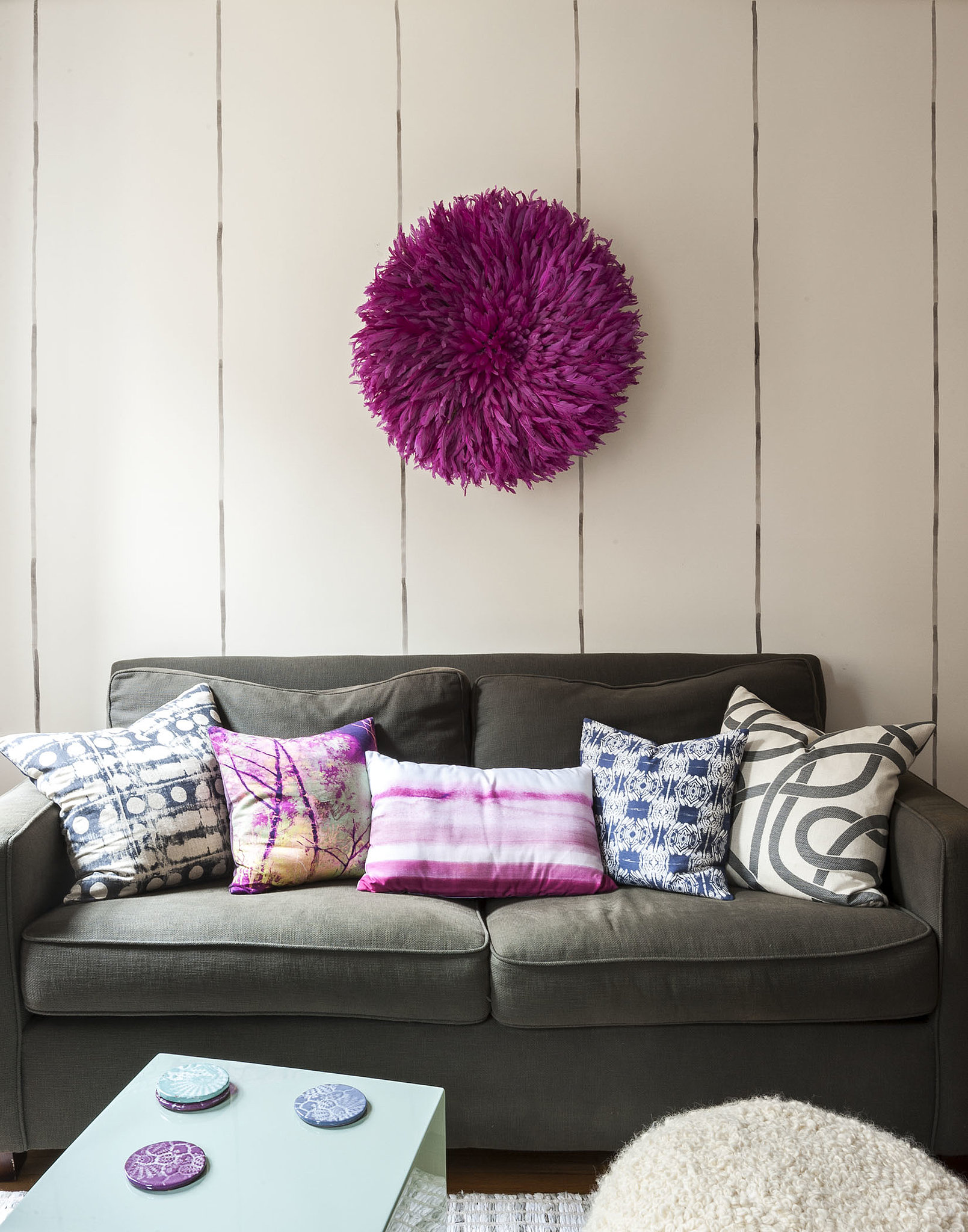 To maximize space, Ali and Lindsay choose side and coffee tables that double as stools for additional seating. To add personality, they hung a magenta juju (African feather headdress) above the sofa. Photo by  Matthew Williams via LABLstudio
