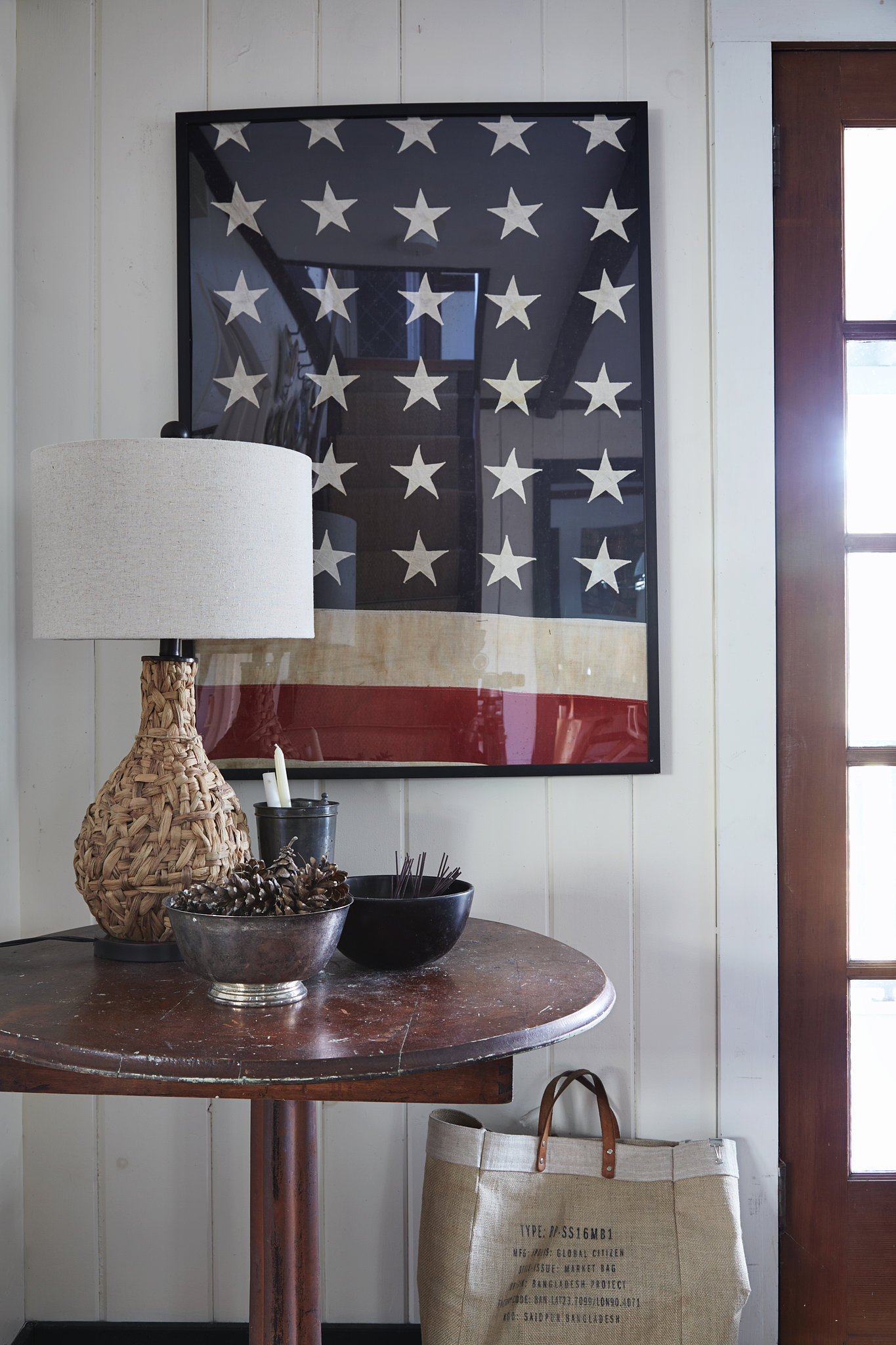 Another piece of Danny's framed flag project hangs above a table with a woven water hyacinth lamp from his home line.  Photo by Armando Rafael Photography