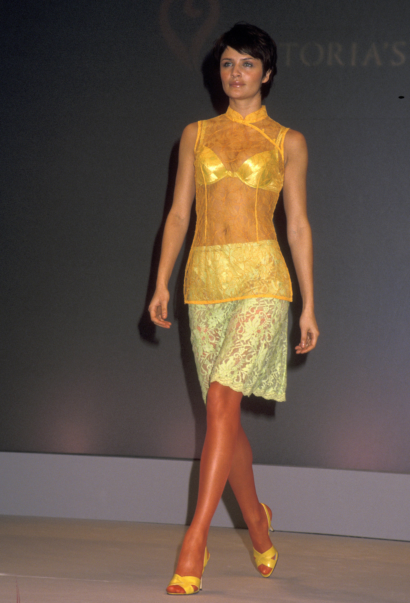 Helena Christensen donned a sheer yellow top and lace skirt on the 1997 runway.