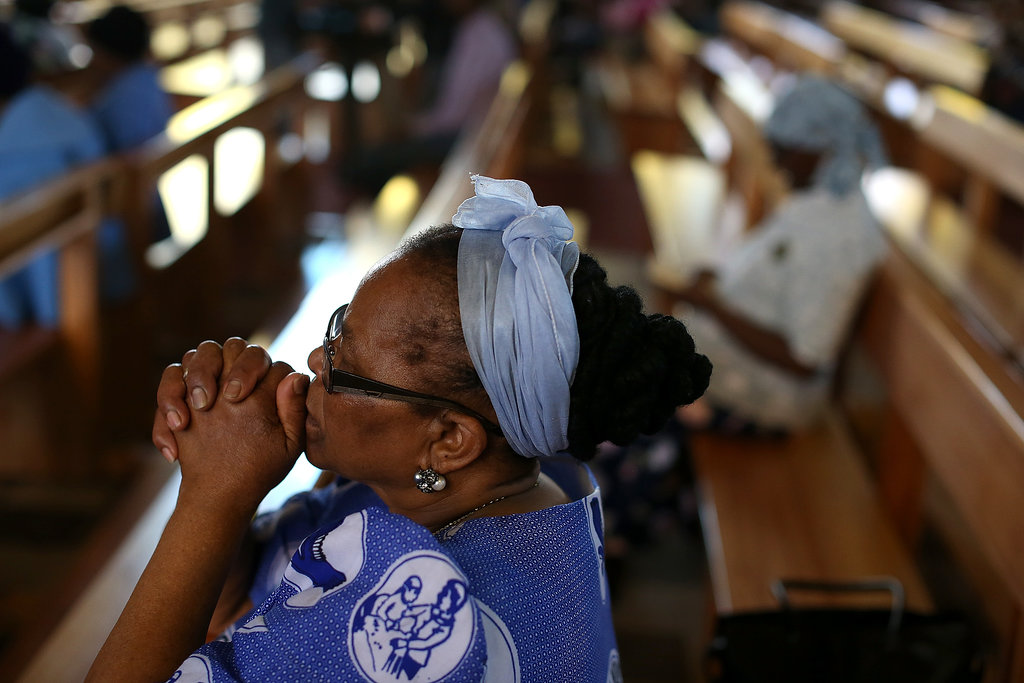 A woman held up her hands and prayed during church services in Soweta, South Africa.