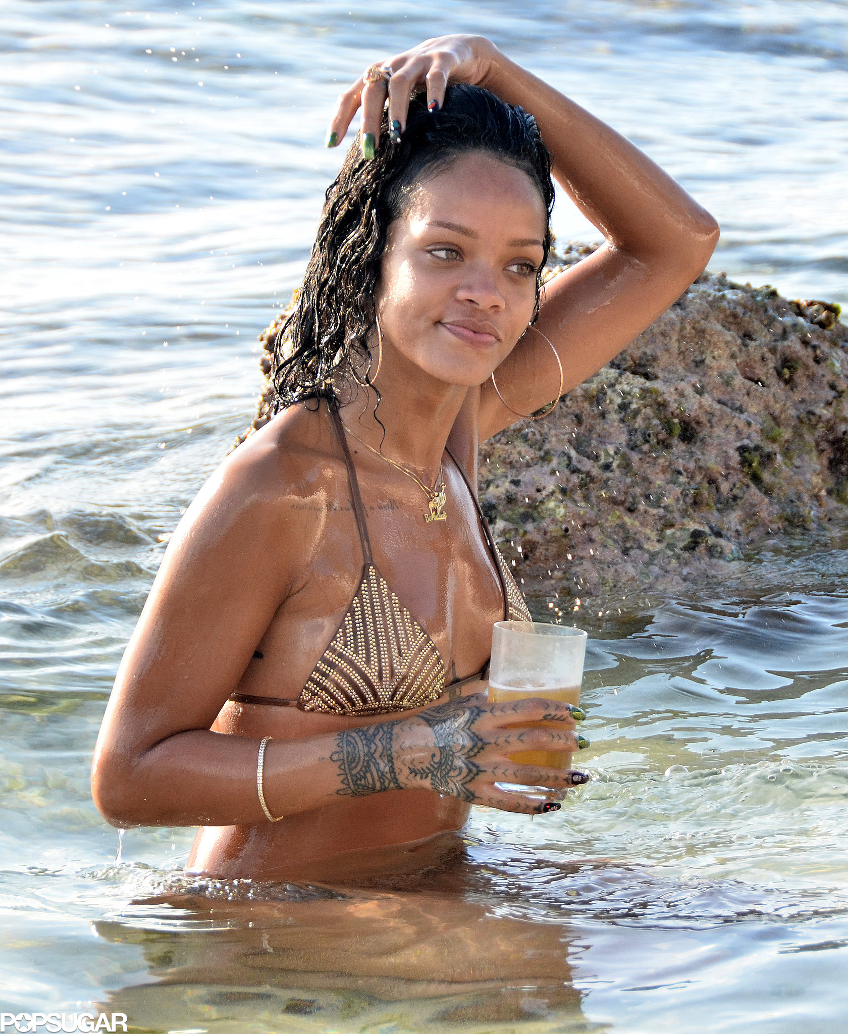 Rihanna relaxed in the water with a drink.
