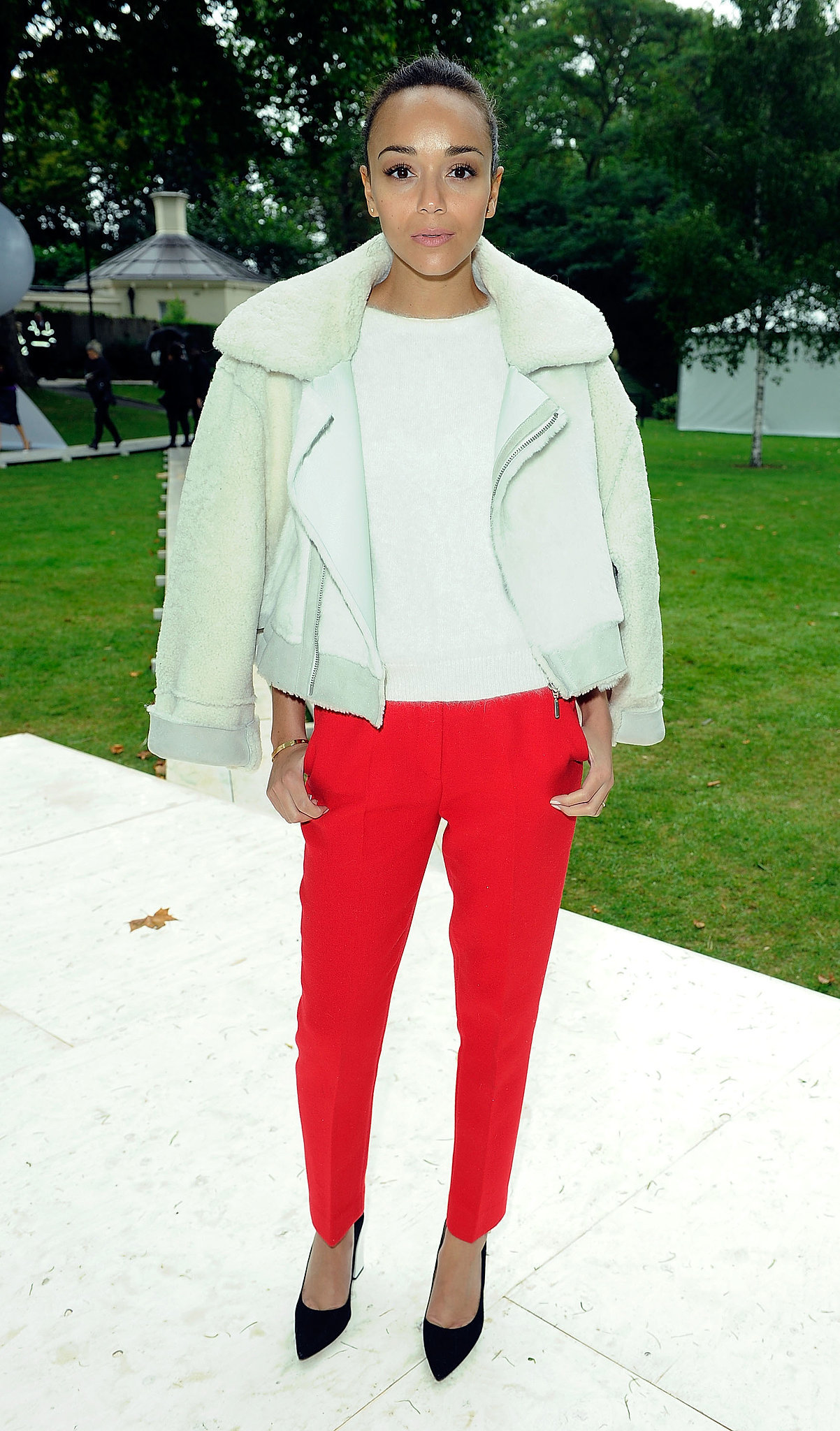At the Topshop Unique show during London Fashion Week Spring/Summer 2014, Ashley Madekwe balanced her bright red trousers with a neutral blouse and coordinating shearling jacket. Where to Wear: A concert.