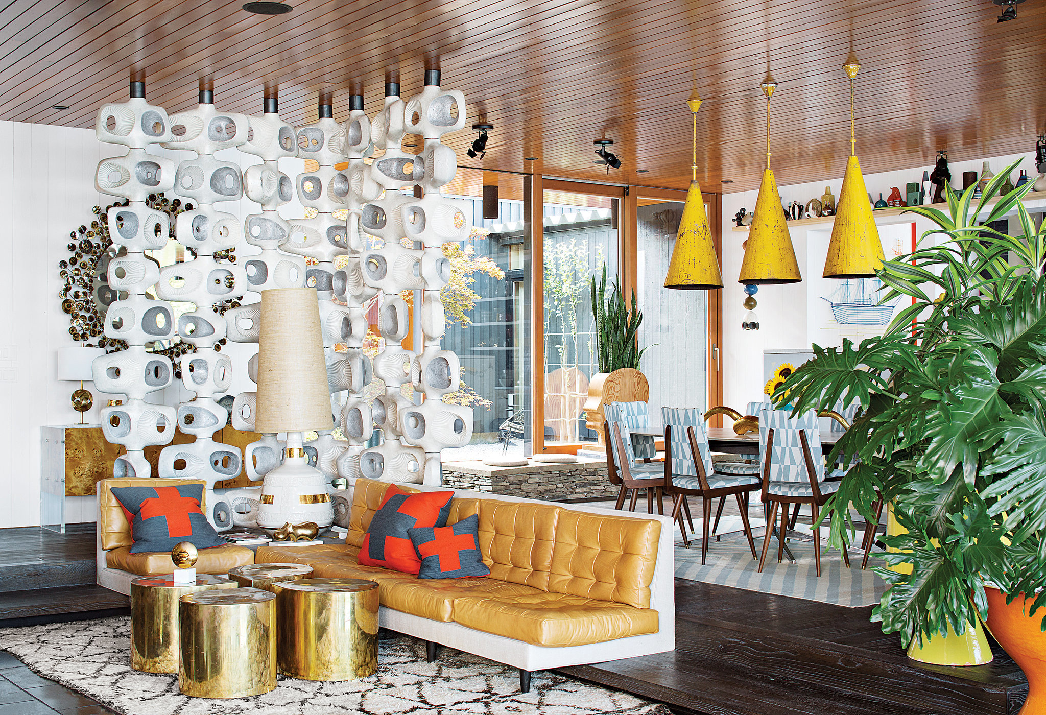 Vibrant and grand yet still inviting, the living room is filled with personality. The room divider is actually concrete and the sofa is seamlessly integrated into the steps. Those yellow pendants? Vintage.  Photo by Floto + Warner via Dwell Magazine