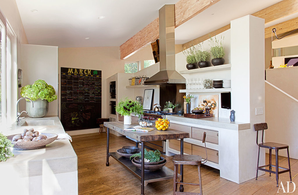 The concrete countertops and sink bring a touch of contemporary cool to the kitchen's rustic wood tones. Source: Roger Davies via Architectural Digest