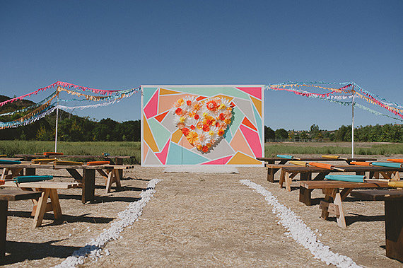 What a fun setup! The bright backdrop pops against any scenery and would make a great photo-booth setting for the reception.  Photo by John Newsome Photography  via 100 Layer Cake