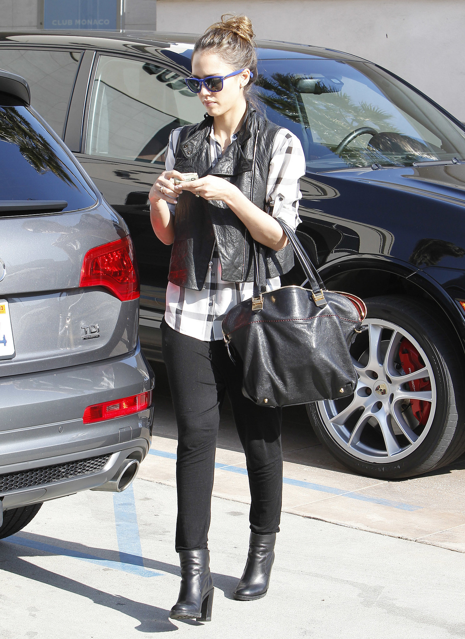 Jessica added a touch of edge to her black-and-white combo — a plaid Madewell top, black denim, and matching ankle booties — by layering a cropped leather vest while out in LA.