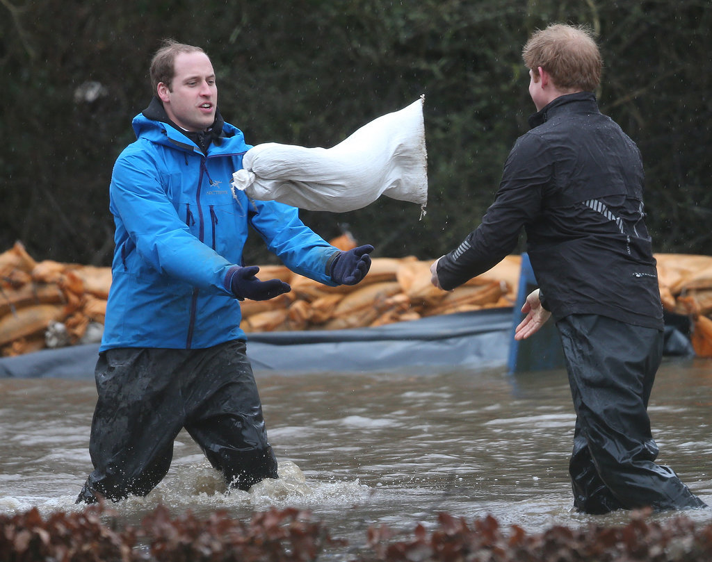 Prince William and Prince Harry got down and dirty with sandbags to help build a flood defense wall at Eton End School in England.