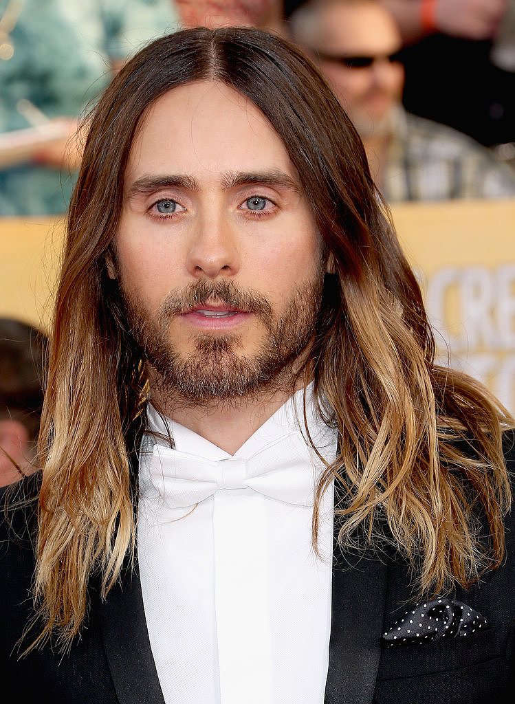 POPSUGAR: Before the Oscars, we polled our readers to see how Jared should wear his hair. The options were beach waves, ponytail bun, or the wet look. The results: 55 percent picked waves, 35 percent picked an up 'do, and 10 percent said the wet look. Our readers had it right! So how did you and Jared reach this monumental decision?  Chase Kusero: We've definitely been experimental, and that's been a key to his hair looking great. He likes to have his style unique to the moment. We did ponytail bun for Golden Globes, and if we did it again, it would seem [old]. We did the Indie Spirit Awards the night before, so he started with product in his hair, and then he slept on it. When he put his jacket on, we knew it had to be down for an iconic vibe. We knew that was it.  PS: What are some tips you can offer our readers to get Jared's undone beach waves at home?  CK: We did subtle things, and it just worked. Yesterday was a big day for him, so his hair was kind of an afterthought. Washing the hair less is the key. Using some sort of wave-enhancing shampoo will add more moisture. That has been the key: moisturising the hair allows it to hang well, have shine, and separate. The more moist the hair is, the more it can wave. Use a flat iron to bend 10 pieces, and it will give it that separation and make it feel undone. But we never use a curling iron or anything on Jared, or it will look too much like glam waves. Straight ends are also the key. Don't go all the way down with the hair iron to keep ends straight. It will make it look more disheveled.  PS: You have said that he doesn't and will never wear extensions. What are some natural tips for growing hair long? Does he get routine trims or eat certain foods? We heard he is a vegan. CK: In the case of a female client, trimming is more of a necessity. When we started the process of growing out his hair, he left it in my hands. So we wanted it to get to a certain point so it doesn't look cut. Trimming it to make it grow is a myth. Yes you need to cut off dead ends, but doing less is better. Not doing color as often, getting less haircuts, washing it even less are all good for the growing process.