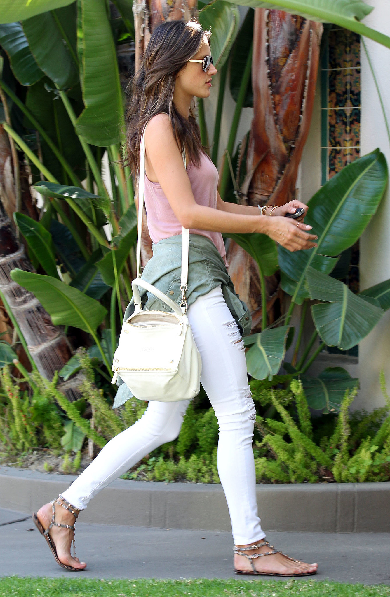 Muted colors combined for an easy off-duty outfit in LA, where the model wore a pink tank top with a green jacket around her waist. For extras, she opted for flat sandals and a Givenchy bag.