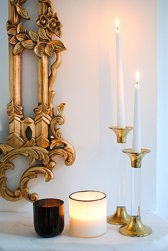 A closer look at the gorgeous details of the mirror and the perfect accoutrements for a well-styled vignette: black and white candles and brass and Lucite candlesticks.  Source: Homepolish