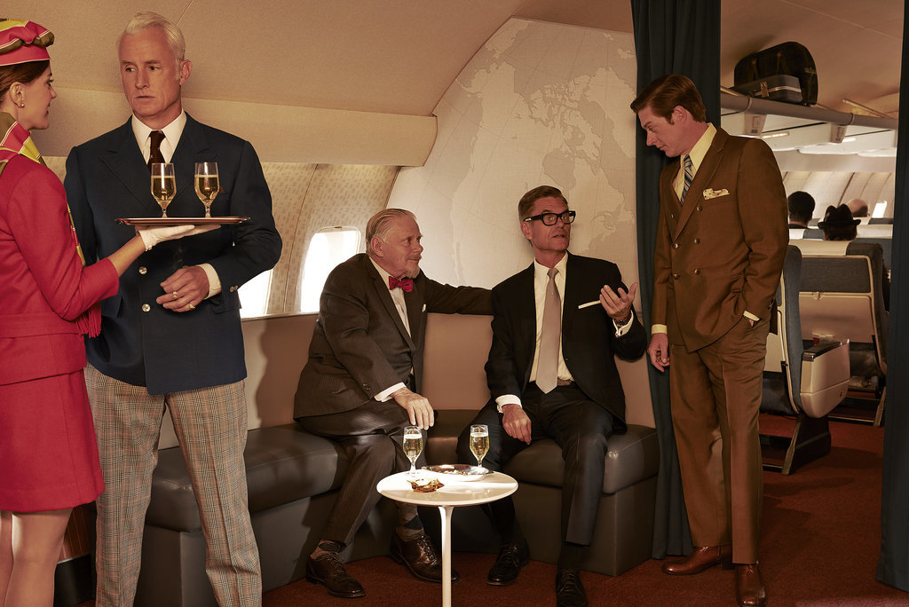 Roger chats up a flight attendant while Bert Cooper (Robert Morse), Jim Cutler (Harry Hamlin), and Ted (Rahm) talk.