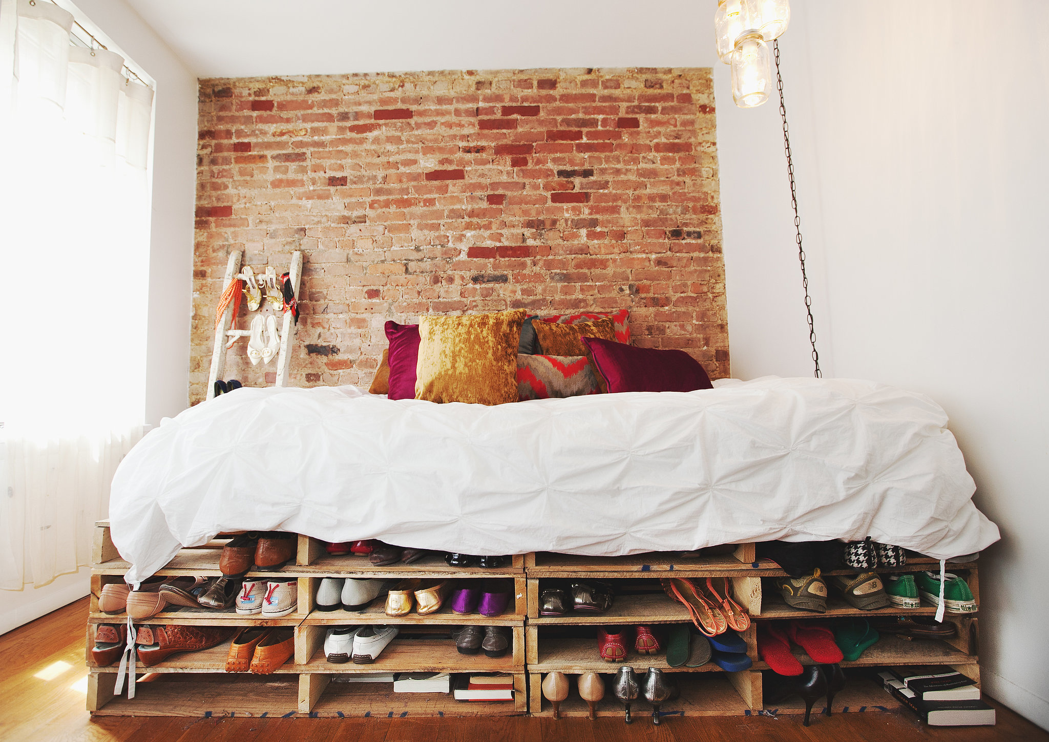 No doubt, the room's focal point is the day bed (that also doubles as a sofa). The frame was made stacking industrial wooden shipping pallets;  a cute and clever way to store shoes!  Photo by Chellise Michael via Homepolish