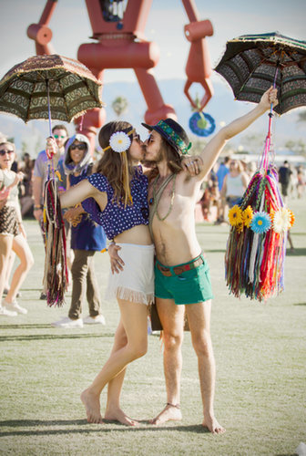 A Coachella couple kissed while holding umbrellas.