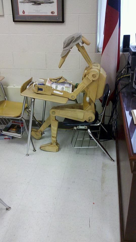 """""""I teach eighth grade and made this scale replica of a Star Wars droid. I dress and pose him depending on what time period we are discussing in class. His name is Roger-Roger. . . . Roger studying for class."""" Source: Reddit user TheVishual via Imgur"""