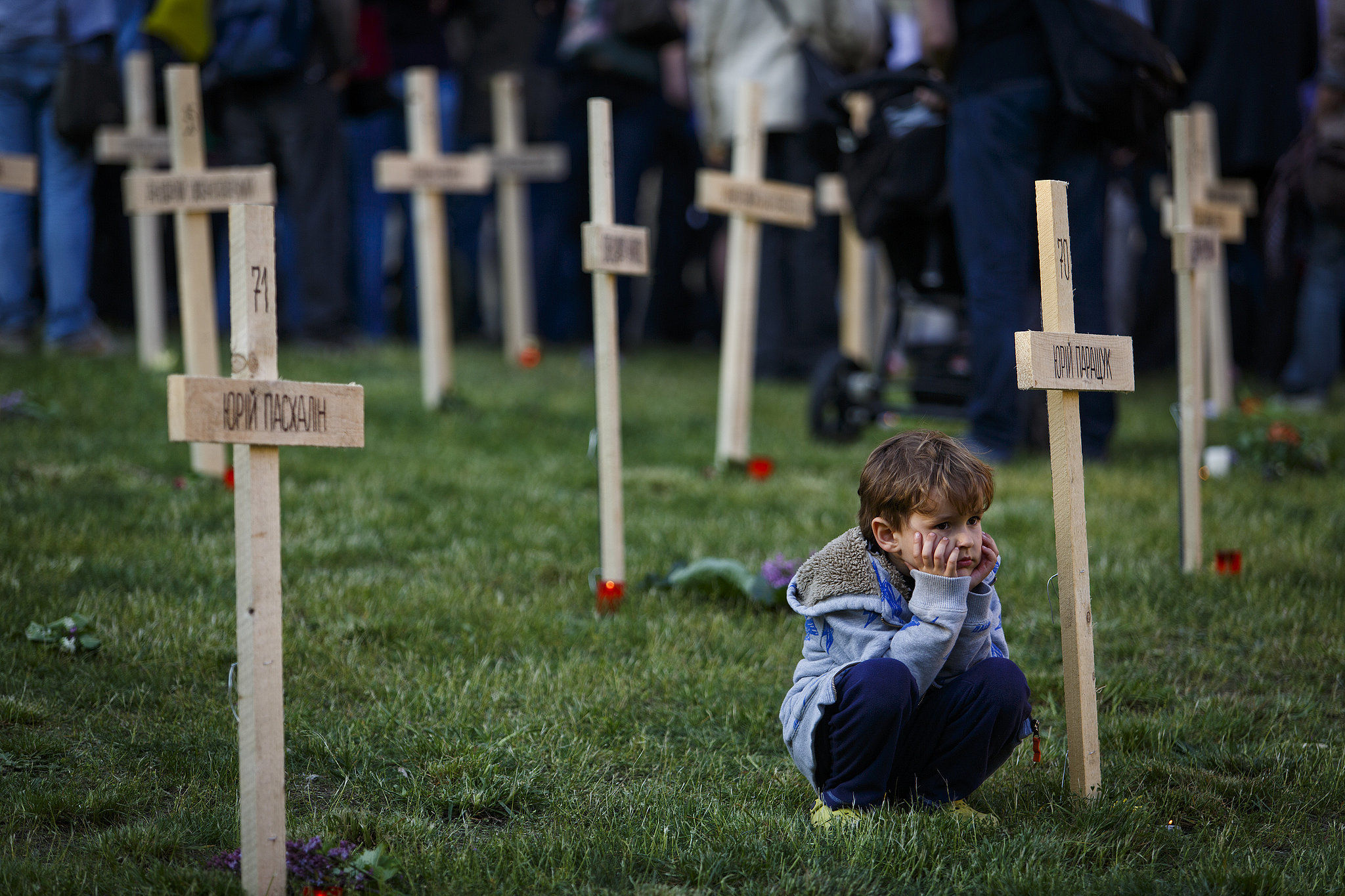 In Prague, the Czech Republic, a young boy sat quietly in a symbolic cemetery for those lost in Ukraine's protests.