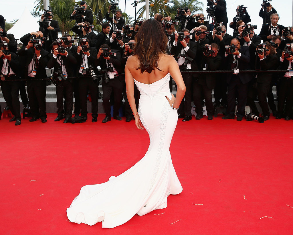 Eva Longoria flaunted her figure in a white gown at the premiere of Saint Laurent.