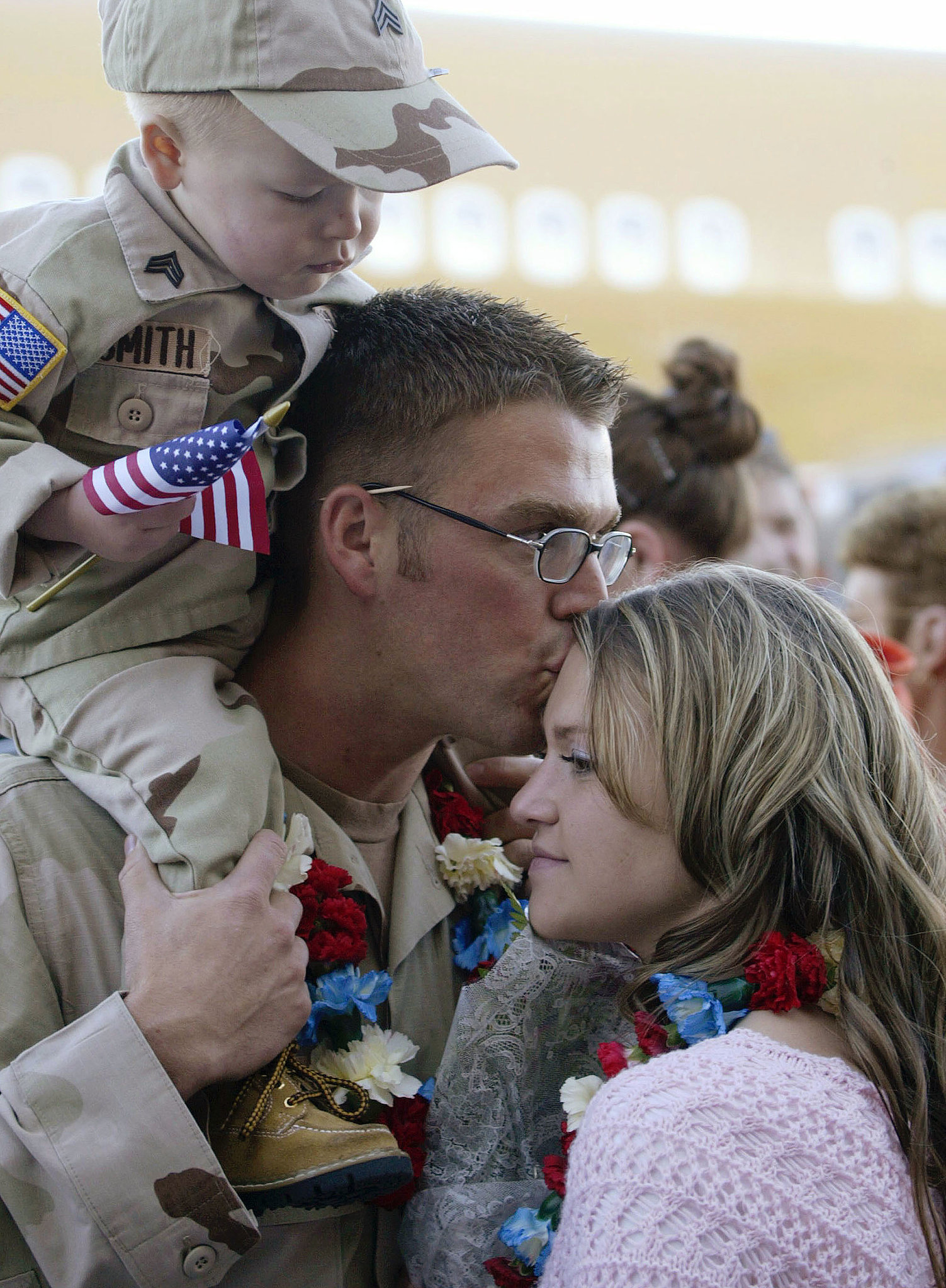 In 2004, Army Sgt. Cody Smith kisses his wife, Kelsie, while his nephew Brandon looks on in Salt Lake City.