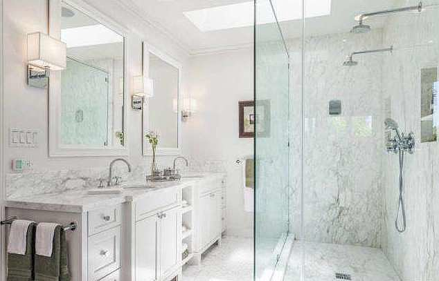 The resort-style master bath offers a large glass shower and soaking tub.   Source: Redfin