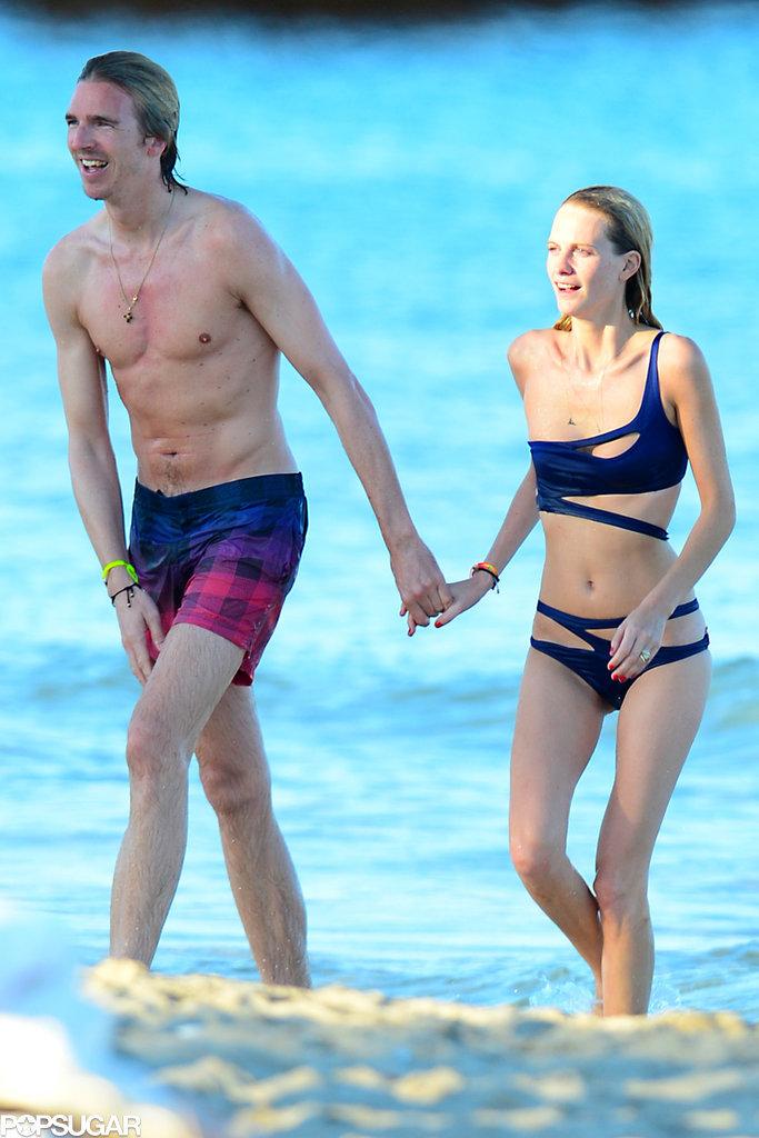 Com uma silhueta esbelta e cabelo loiro médio sem sutiã (tamanho 32B) em biquini na praia