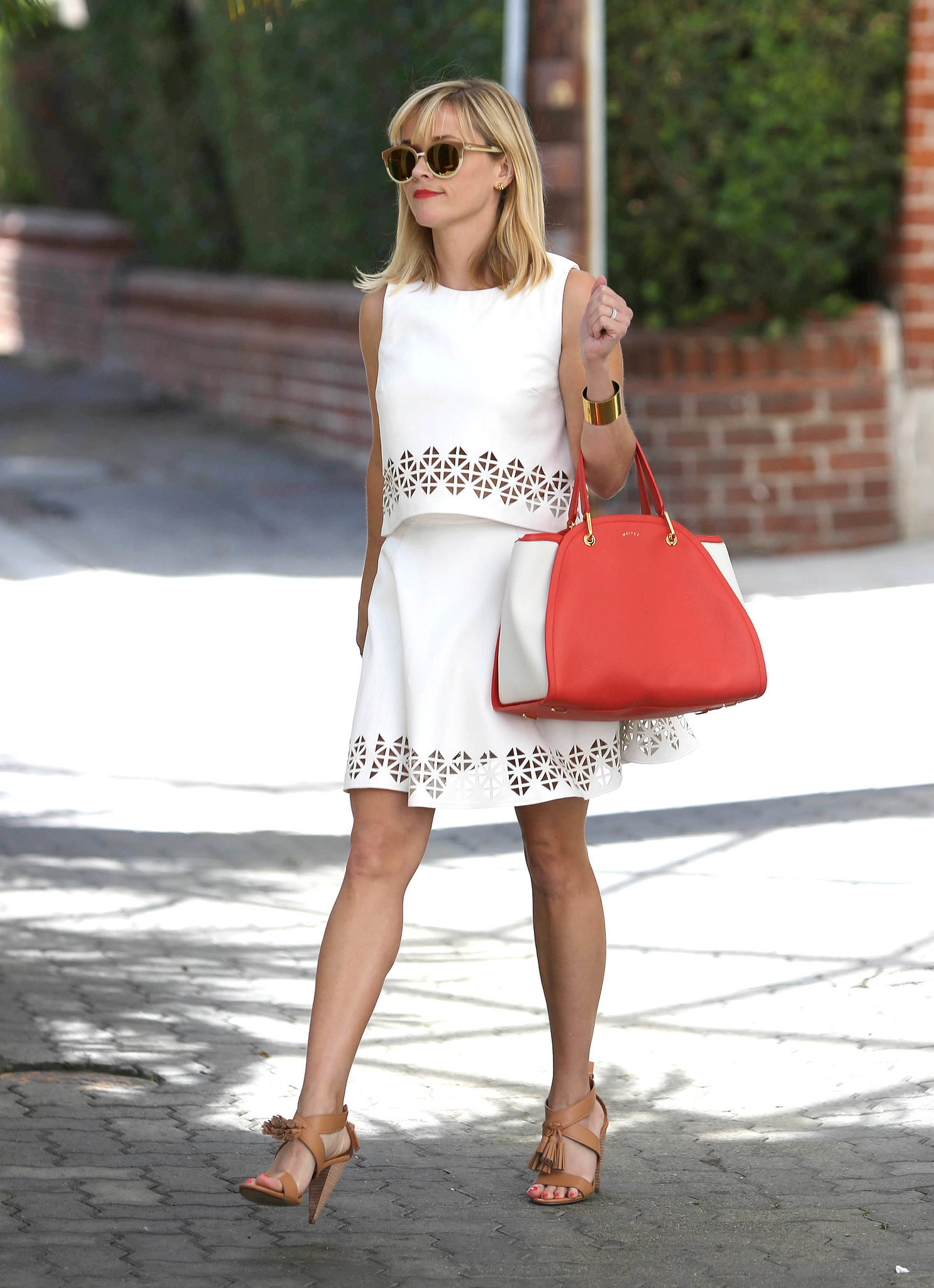 Reese slipped on her Monica Rose for Lovers + Friends two-piece number and then piled on the accessories. With two-tone Tory Burch sunglasses; her Maiyet tote; tan, tassel-embellished heels; and a simple bangle, she's nailed the sophisticated prep look. The playful vibe her flouncy skirt's giving off is just the icing on the cake. Source: Getty / SMXRF/Star Max