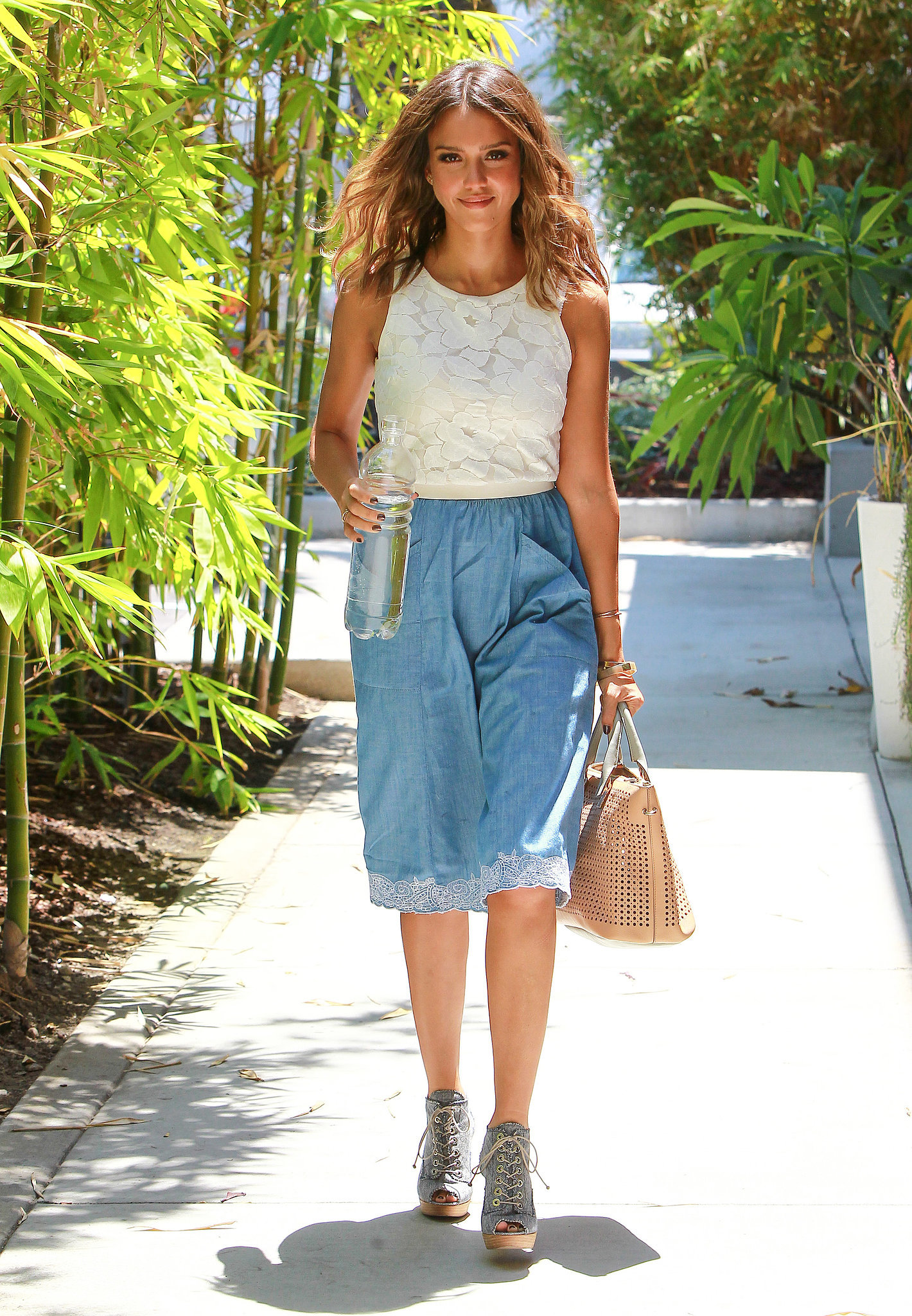 Jessica's got a lot going on. There's the double-denim appeal of her lace-up booties and Topshop pocket skirt. Then there's the white embroidered hem, which complements her floral Tart Collections crop top and lends her look a light, feminine touch. And she finishes with the addition of her perforated Chloé Baylee tote and a few Phyllis + Rosie hammered cuffs. Ultimately, we realized that this look is all about finding the right neutral separates that still maintain enough oomph to turn heads. In other words, it's all in the details. And, lucky for you, we've laid them out, below.