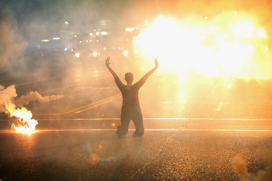 A women knelt in the streets with her hands up as tear gas filled the air.
