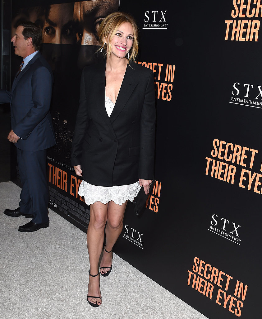 Julia layered an embroidered white dress with a scalloped hemline beneath her Givenchy blazer and held onto a black clutch.