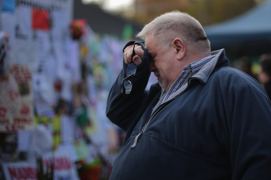 A man cried while standing at the tribute wall outside the hospital.