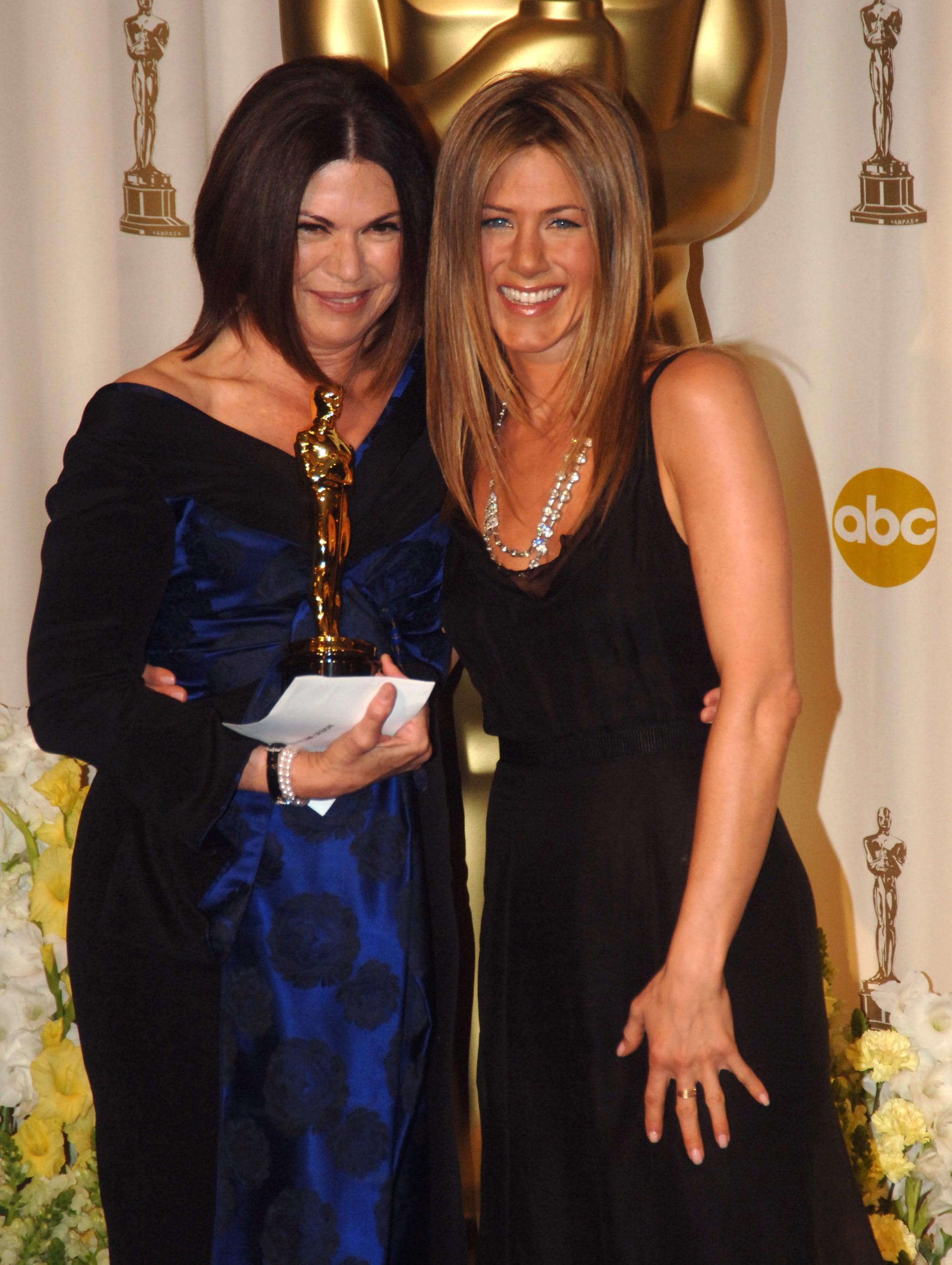 Jennifer Aniston posed in the press room with Colleen Atwood after  presenting her with the statue for best costume design for Memoirs of a Geisha in 2006.
