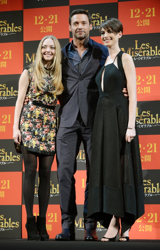 Amanda and Anne both flanked costar Hugh Jackman at the film's Tokyo premiere. Amanda gave a floral Brood dress a makeover with black tights and booties; Anne took the retro-inspired glam route in a fit-and-flare Antonio Berardi.