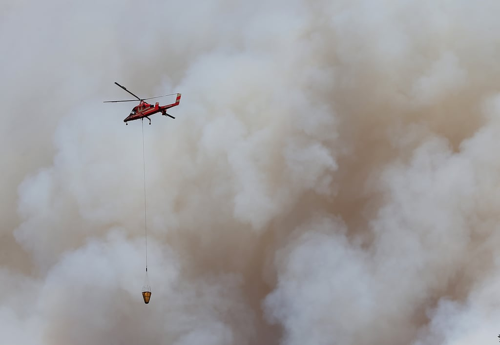 A helicopter flew near a giant plume of smoke.