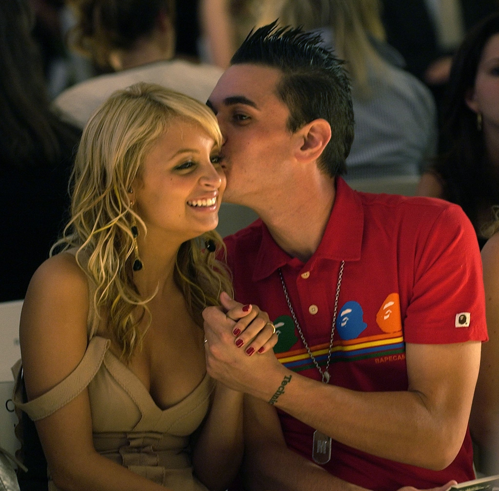 Nicole was given a sweet smooch by her then-boyfriend, the late DJ AM, as they sat front row for the Monique Lhuillier runway show in September 2004.