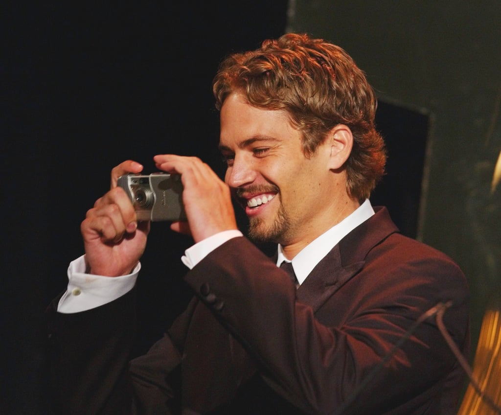 He smiled while snapping photos at the Hollywood Film Festival Awards in August 2001.