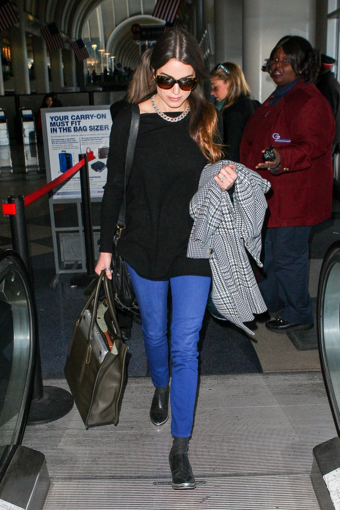 Nikki Reed nails airport dressing in blue jeans and a long-line black top.