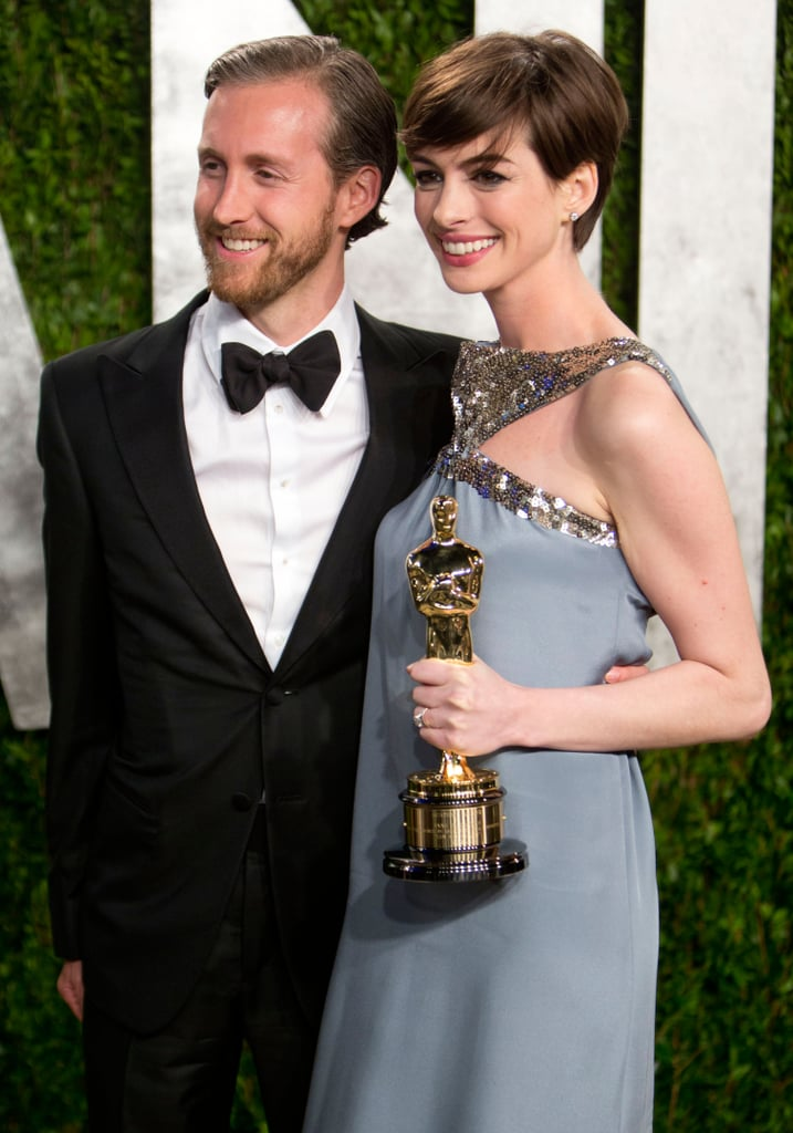 Anne Hathaway took photos with her husband at the Vanity Fair Oscar party.