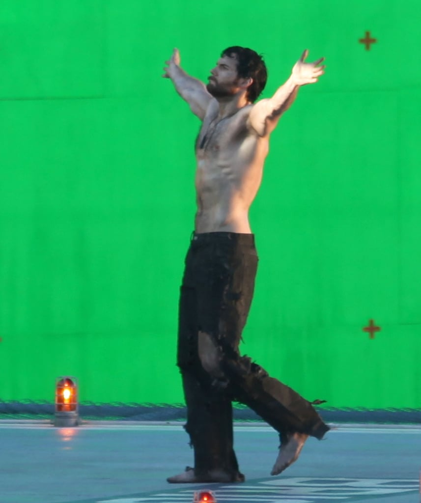 Shirtless Henry Cavill put his hands up.