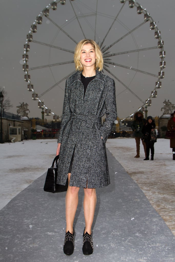 Rosamund Pike donned a little black dress with studded booties, then finished off her Parisian look with a tweed coat and a black Dior satchel.