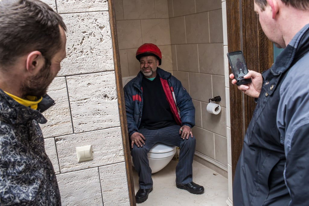 A man posed for a picture on one of the toilets at the estate.