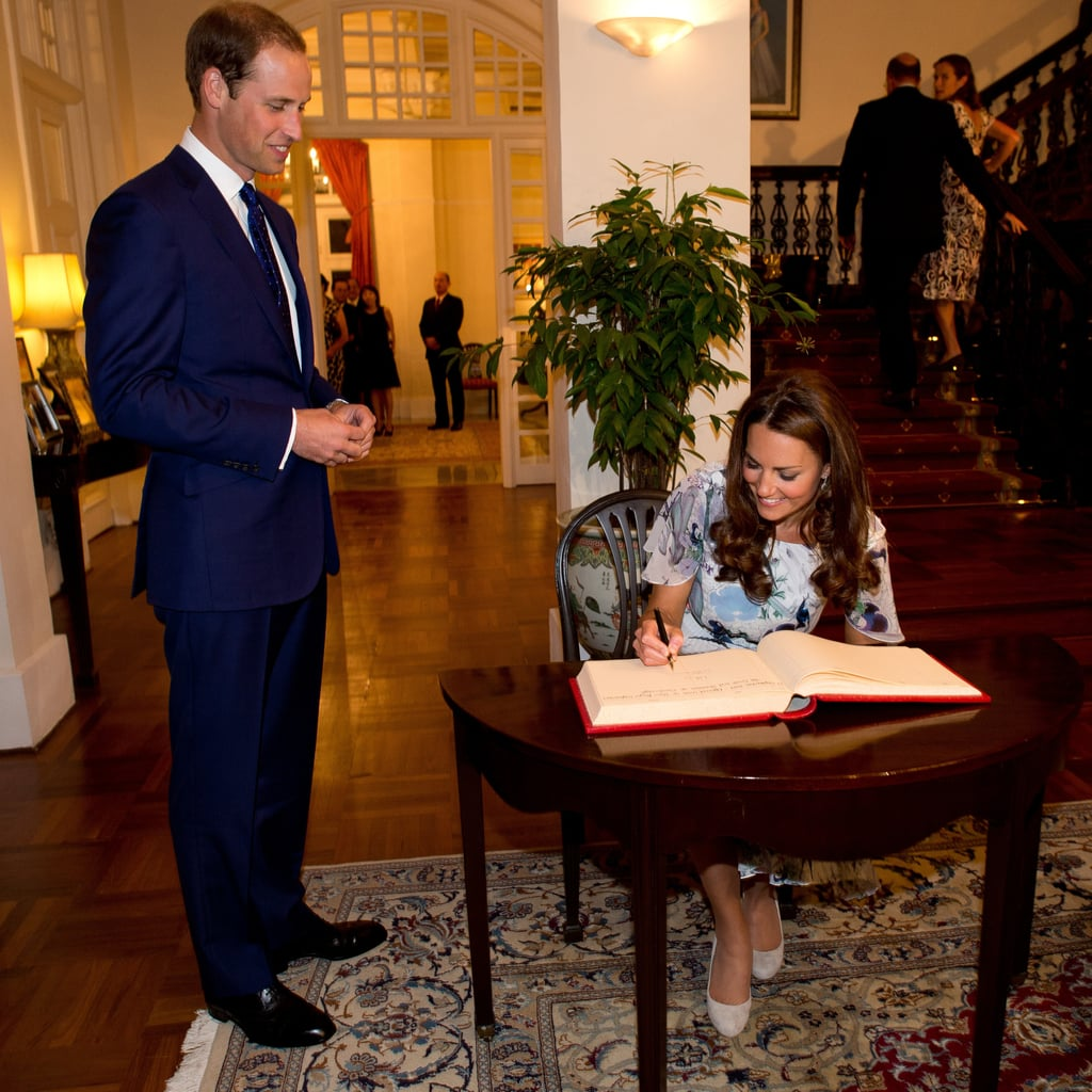 Prince William smiled as Kate Middleton signed a guest book at a residence in Singapore.