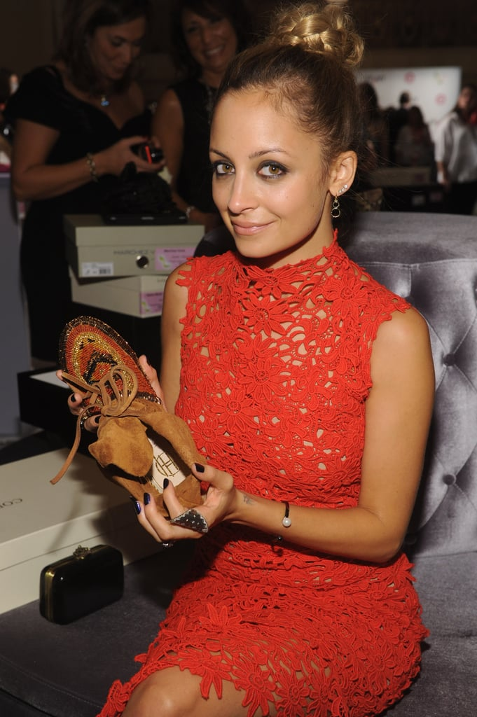 Nicole Richie held up a shoe while attending the event.