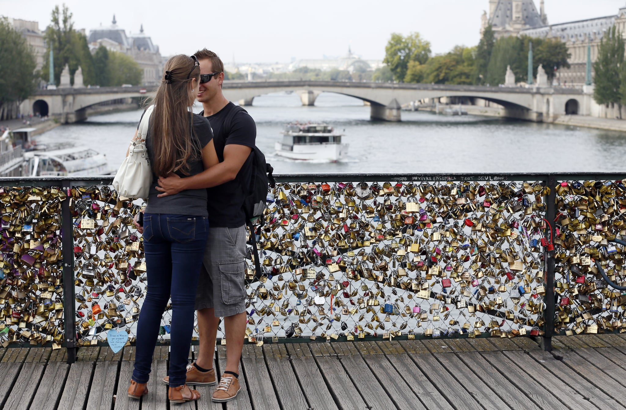 A couple embraced by their love lock in Paris.